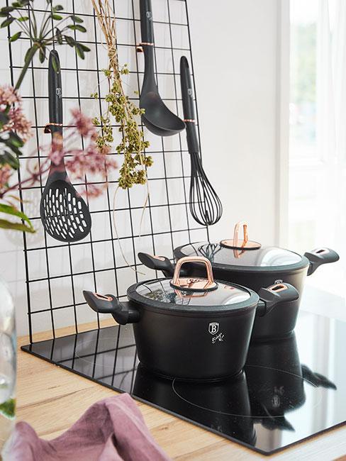 Czarne naczynia z żeliwa na płycie indukcyjnej obok wiosennych kwiatów