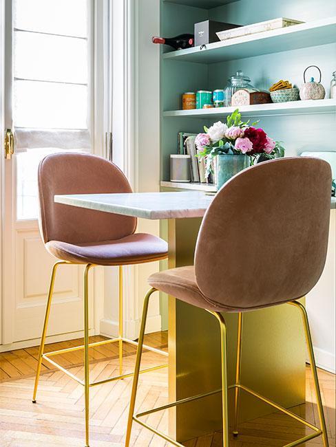Mały wysuwany stolik w aneksie kuchennym z różowymi krzesłami barowymi