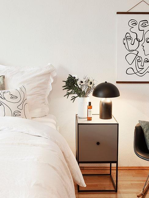 Zbliżenie na minimalistyczną szarą szafkę nocną i czarną lampę obok łóżka z białą pościelą