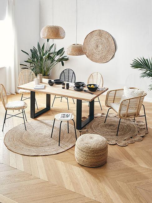 jadalnia w stylu boho z różnymi krzesłami z rattanu i dużym prostokątnym stołem z jasnego drewna