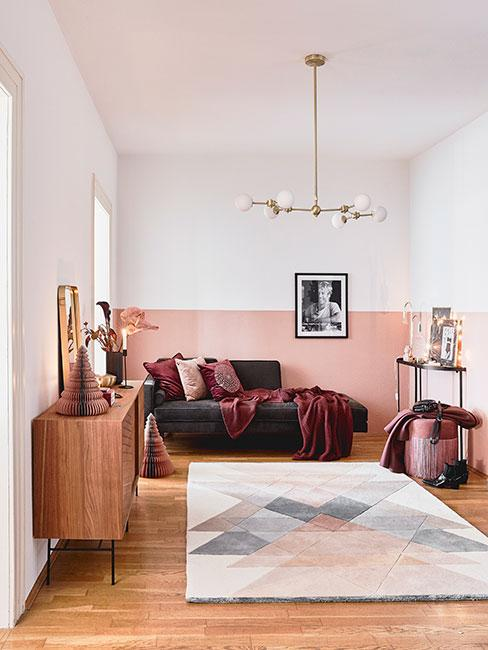 Mały salon z bordowym szezlongiem z aksamitu, drewnianymi meblami i pastelowym dywanem