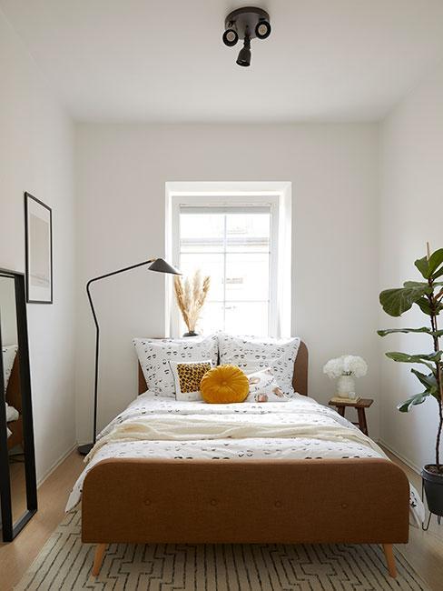 mała sypialnia z brązowym łóżkie i białą pościelą w rysunkowe wzory
