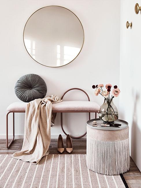 Przedpokój w stylu glamour z óżową ławką z aksamitu, dużym lustrem w złotej ramie i beżowym pufem z frędzlami z aksamitu