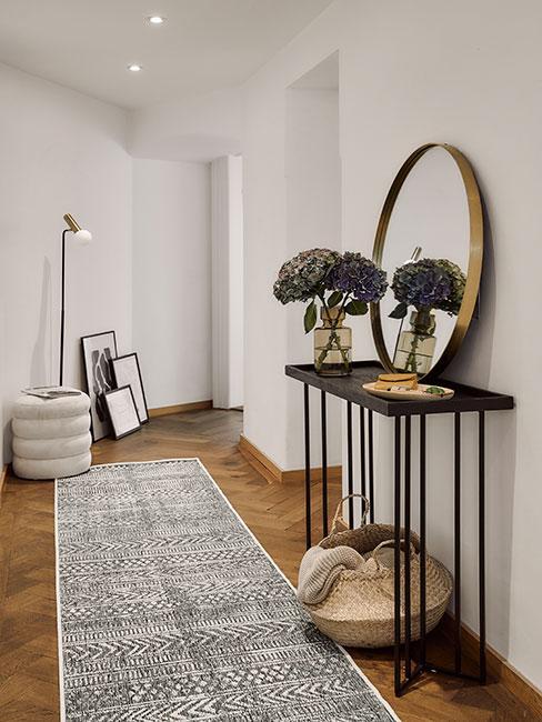 Wąski przedpokój z długą lampą stojącą, czarną konsolą na której stoi okrągłe lustro i koszem z trawy morskiej