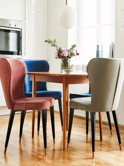Jadalnia w kącie kuchni z drewnianym stołem oraz krzesłami z aksamitnym obiciem