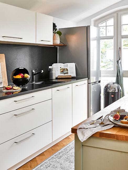 wąska kuchnia z białymi szafkami i ciemną ścianą
