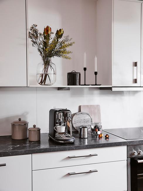 Biała kuchnia z białymi frontami szafek, półką z dekoracjami oraz akcesoriami kuchennymi