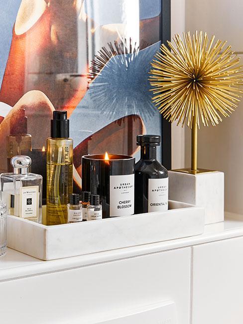 zbliżenie na tacę dekoracyjną z marmuru z perfumami, i kosmetykami w pięknych flakonikach na tle abstrakcyjnego obrazu