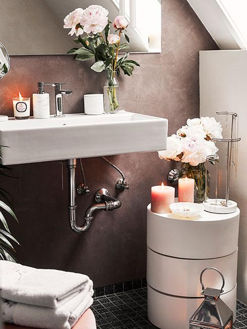 Zbliżenie na romantyczną łazienkę z białym stolkiem pomocniczym, na którym są różowe kwiaty w wazonie i świeczki