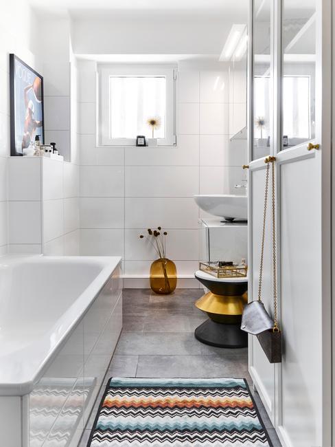 Długa łazienka z wanną, kolorowym dywanem oraz małymi dekoracjami