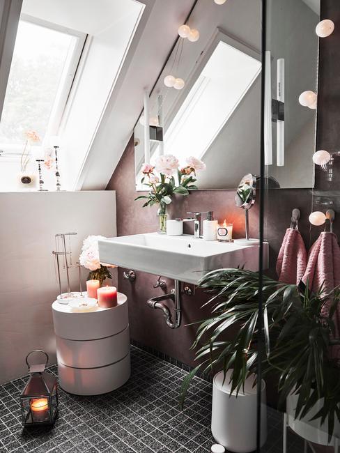 Łazienka na poddaszu z prysznicem i umywalką, szafką na przechowywanie oraz lampkami cotton balls