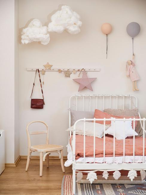 białe, metalowe łóżko w pokoju dziecięcym z drewnianym krzesłem i kilkoma lampami