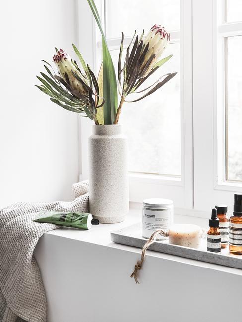 Parapet w łazience z tacą dekoracyjną z kosmetykami, wazonem z proteą oraz ręcznikim