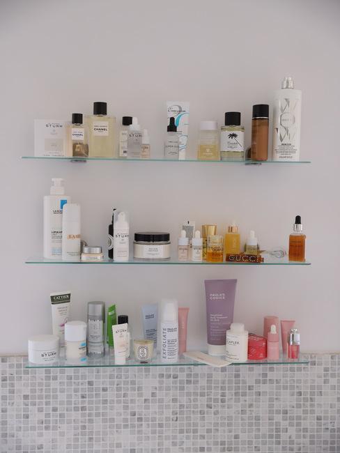 Zbliżenie na trzy szklane półki w łazience z kosmetykami