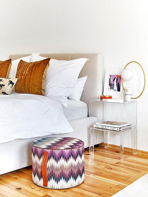 Sypialnia w stylu etno z wzorzystym pufem, rdzawymi poduszkami oraz stoliczkiem nocnym z plastiku