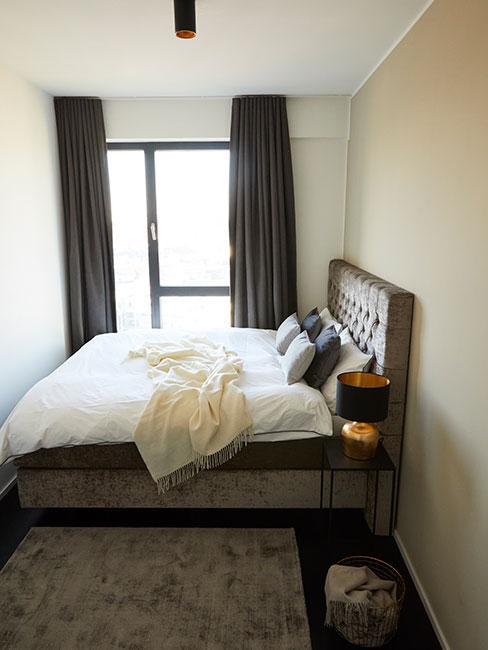 Mała sypilania z ciemnym tapicerowanym łóżkiem ustawionym w poprzek