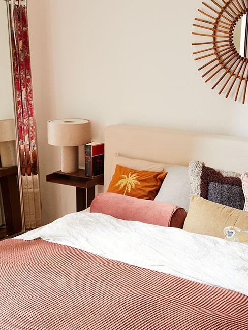 Zbliżenie na łóżko w stylu boho z kolorowymi poduszami, różowym pledem, czarnym stolikiem nocnym z lampką