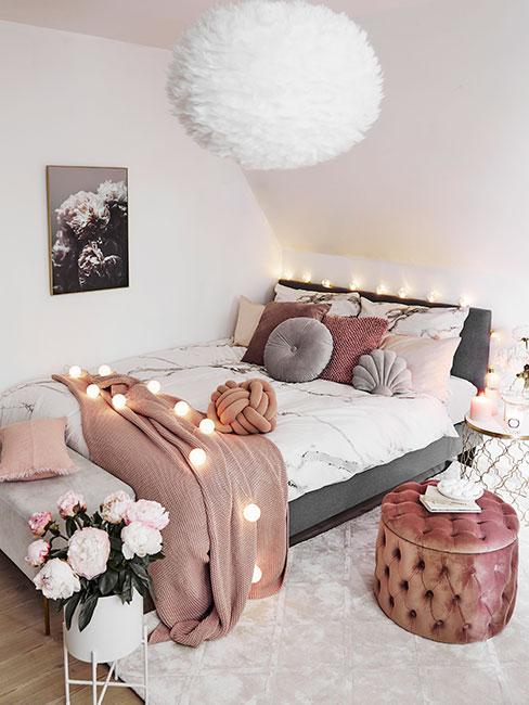 Biała sypialnia z łóżkiem o szarej ramie, różowym pledem, różowym pufem oraz lampkami cotton balls