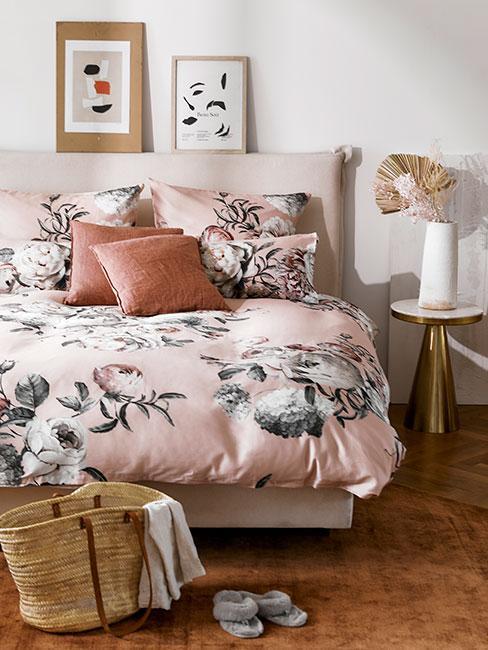 Biała sypialnia z łóżkiem z różową pościelą, stolikiem z wazonem oraz dekoracyjnymi obrazkami