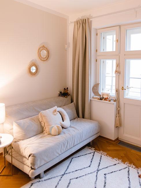 Zbliżenie na szarą, rozkładaną sofę z poduszkami nad którą wiszą okrągłe lusterka