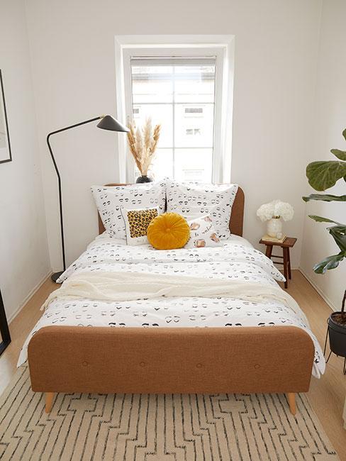 Mała sypialnia z brązowym łóżkiem, jasną pościelą, żółtą poduszką i czarną lampą podłogową