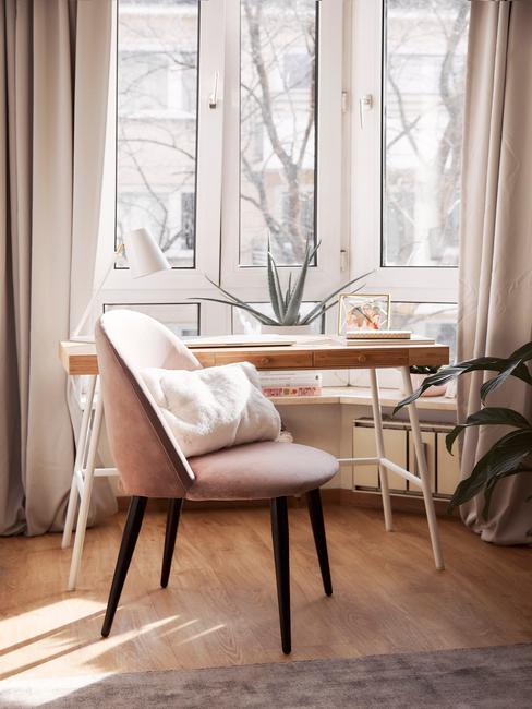 Kącik do pracy w sypialni z biurkiem o drewnianym blacie, różowym, tapicerowanym krześle oraz roślinami