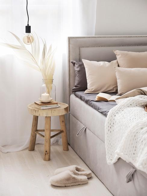 Szare łóżko z zagłowkiem, beżowymi poduszkami, drewnianym stolikiem nocnym, wazonem z trawą pampasową