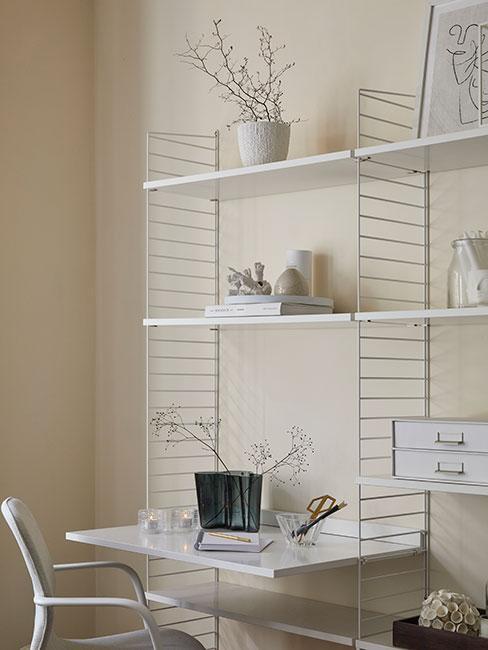 Białe biurko przy białym minimalistycznym ażurowym regale
