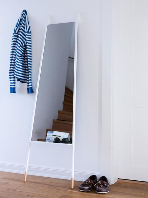 Duże, stojące lustro w przedpokoju obok pary butów i wieszka na ubrania