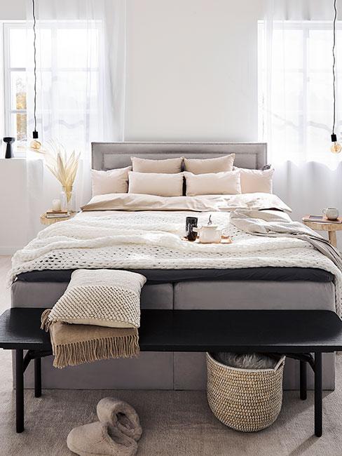 Szare łóżko z funkcja przechowywania w jasnej sypialni