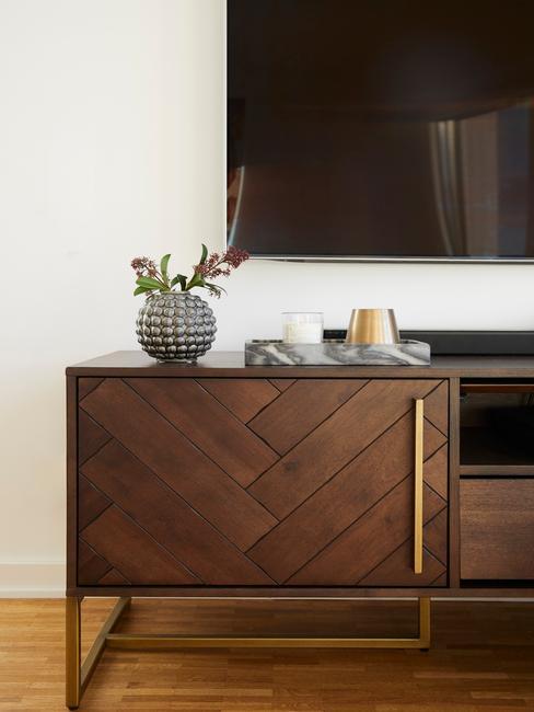 Drewniana komoda z ciemnobrązowym kolorze z dekoracjami nad którą wisi telewizor