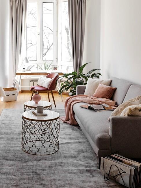 Kawalerska z szarą, rozkładaną sofą, białymi sotliczkami kawowymi z wazonami, szarnym dywanem, częścią do pracy z biurkiem i różowym krzesłem oraz rośliną