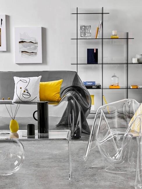 szara sofa w nowoczesnym salonie z żółtą poduszką i przezroczystym fotelem