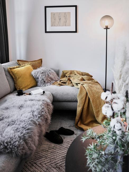 szara sofa narożna z szarym futerkiem i żółtymi tekstyliami