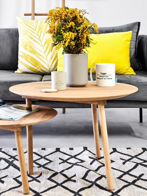Zbliżenie na drewniany stolik na tle szarej sofy z żółtymi poduszkami