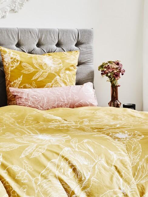 szare łóżko z żółtą pościelą w kwiaty