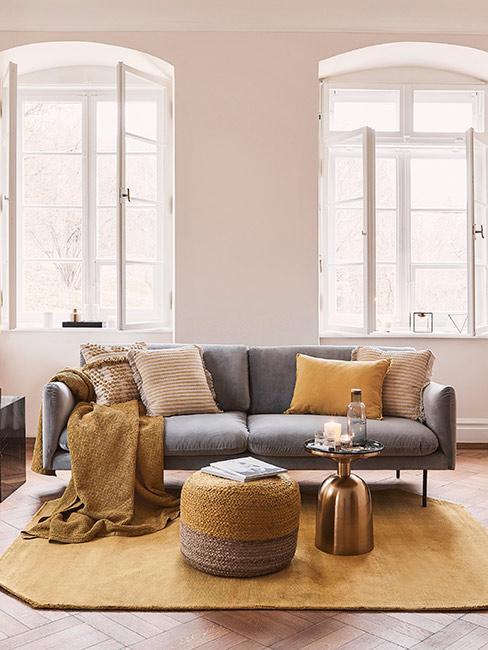 Aranżacja w stylu boho z szara sofą z aksmaitu, żółtą pufą i dywanem oraz żółtymi poduszkami