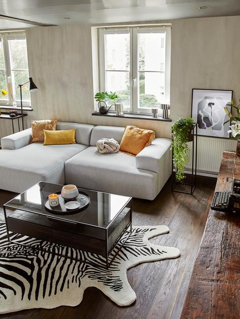 salon w stylu retro z dywanem w zebrę, szarą sofą modułową i żółtymi poduszkami