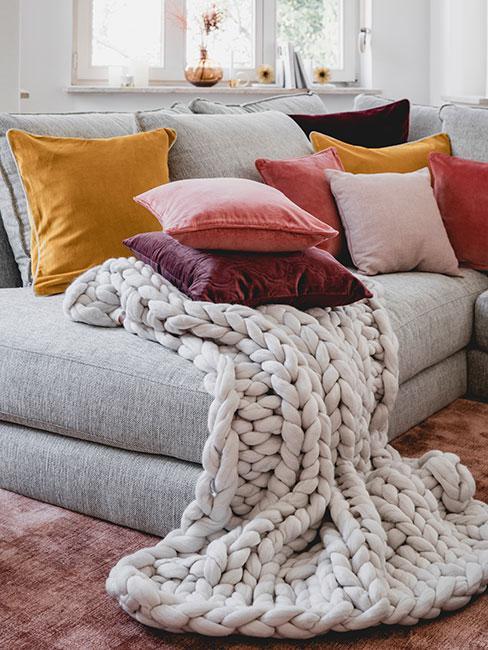 Zbliżenie na szarą sofę z żółtymi, różowymi i czerwonymi poduszkami
