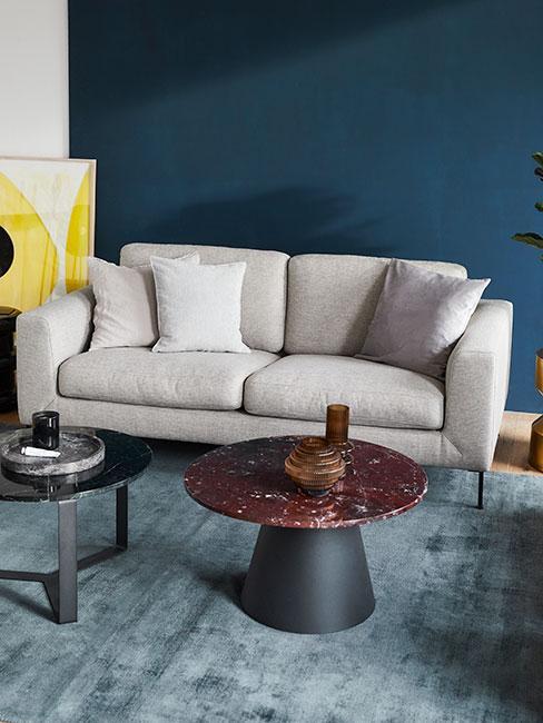 Szara sofa na tle niebieskiej ściany ze stolikiem bordo