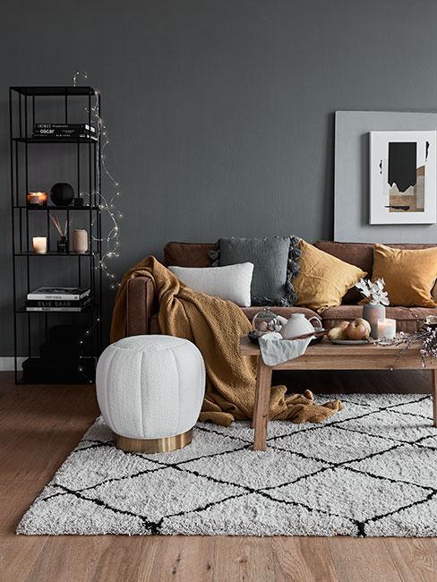 brązowa skórzana sofa na tle szarej ściany z ciemnożółtymi poduszkami i beżowym pufem bucle