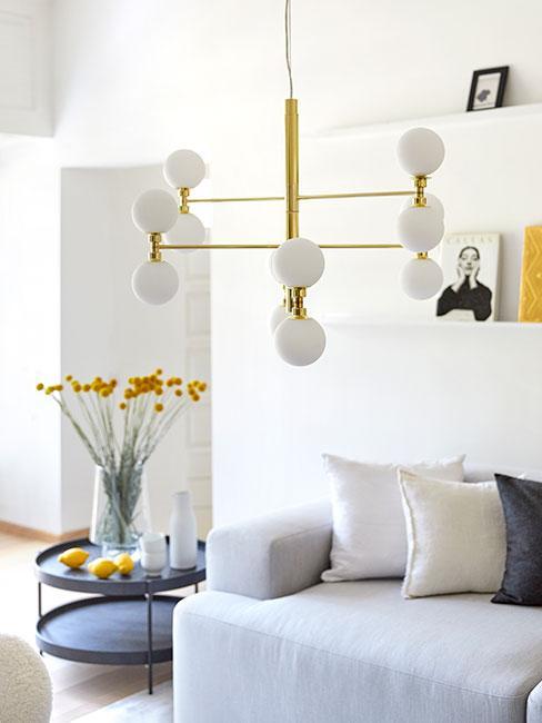 Zbliżenie na złotą wieloramienna lampę z białymi okrągłymi kloszami z szarą sofą w tłe i żółtymi kwiatami w wazonie na czarnym stoliku