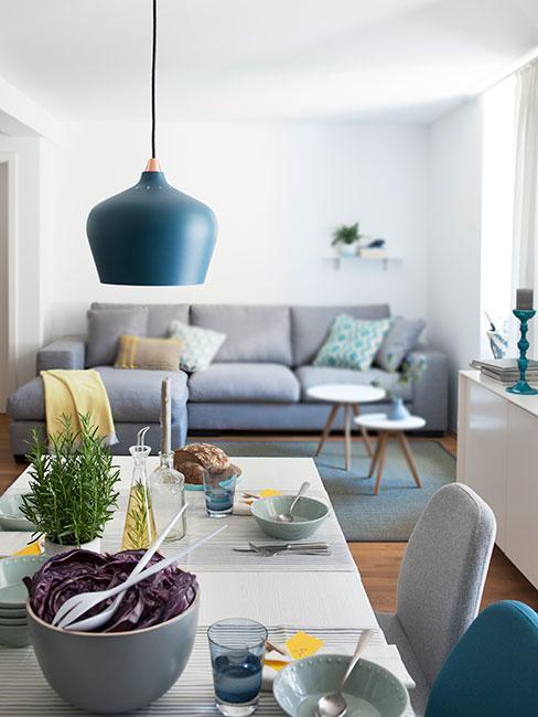 Zbliżenie na modrą lampę nad stołem z szarą sofą w tle i żółtymi poduszkami