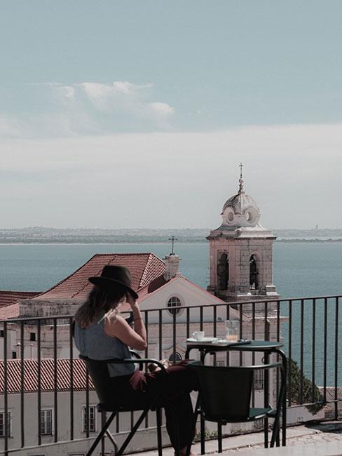 Kobieta sidząca na placu w Lizbonie z widokiem na port