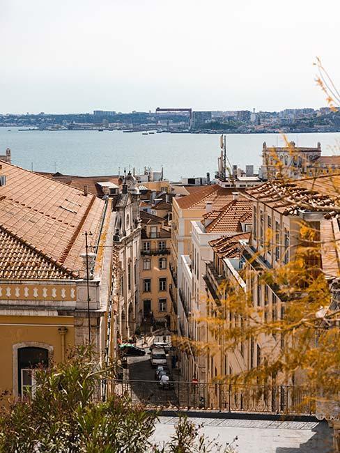 Pomarańczowe dachy Lizbony z oceanem w tle