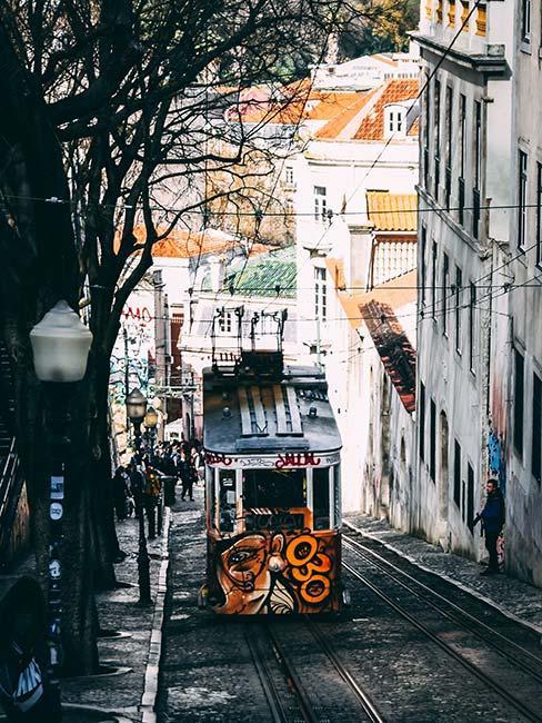 żółty tramwaj pokryty grafitti na stromej uliczce w Lizbonie