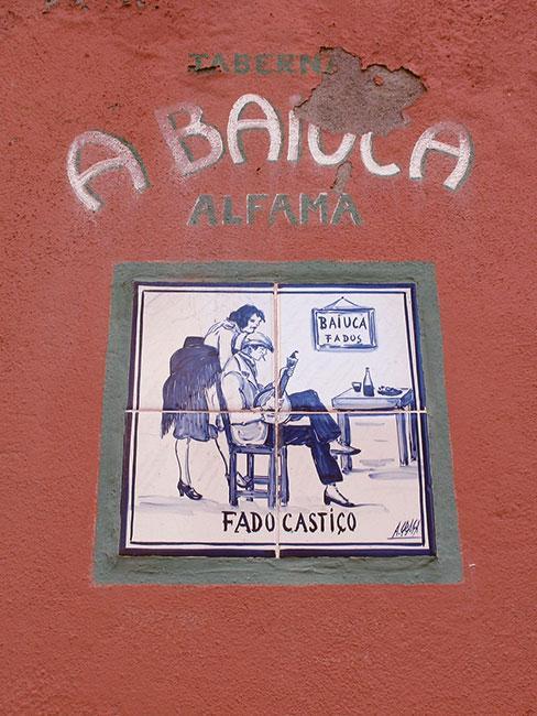 Zbliżenie na żłytkę azulejo z obrazkiem muzyka fado i kobiety w lizbońskiej Alfamie