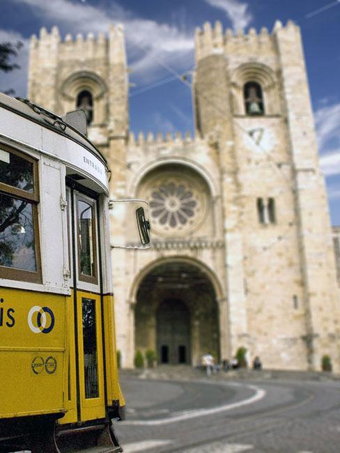 żółty Lizboński tramwaj na tle katedry