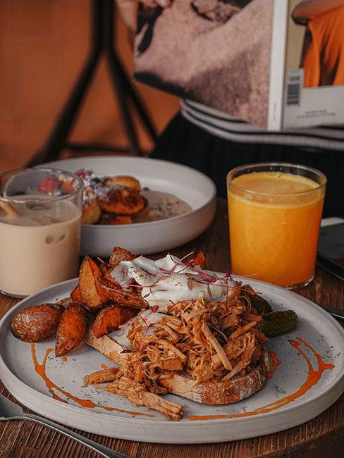 Zbliżenie na wieprzowinę z ziemniakami na talerzu obok soku pomarańczowego w kawiarni Seagull Method Cafe w Lizbonie