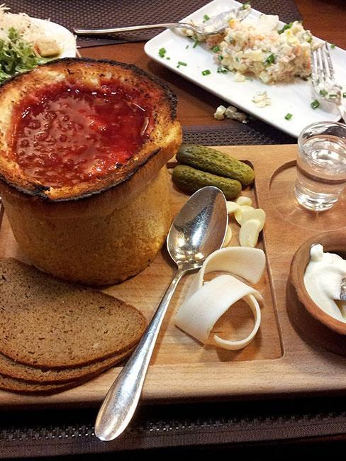 Barszcz litewski w chlebie z kieliszkiem wódki na drewnianej desce z chlebem